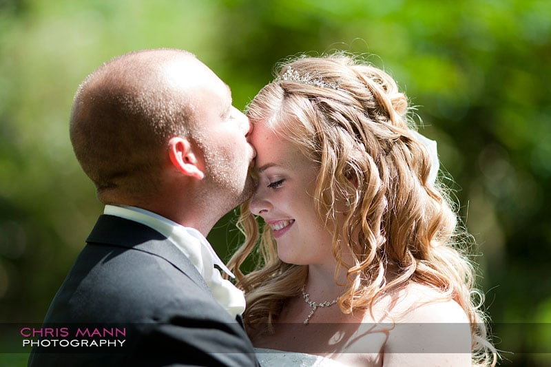 a kiss for the bride - Libby and Paul's wedding at Cisswood House - photo by Chris Mann Photography