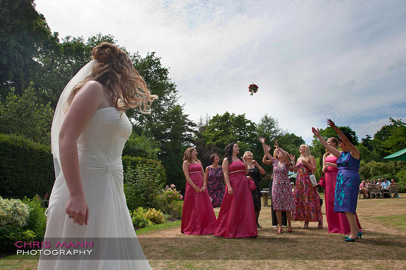 tossing the bouquet - Libby and Paul's wedding at Cisswood House - photo by Chris Mann Photography