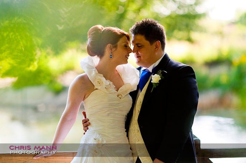 Kimberley & Richard at Bentley - bride and groom at railing by lake