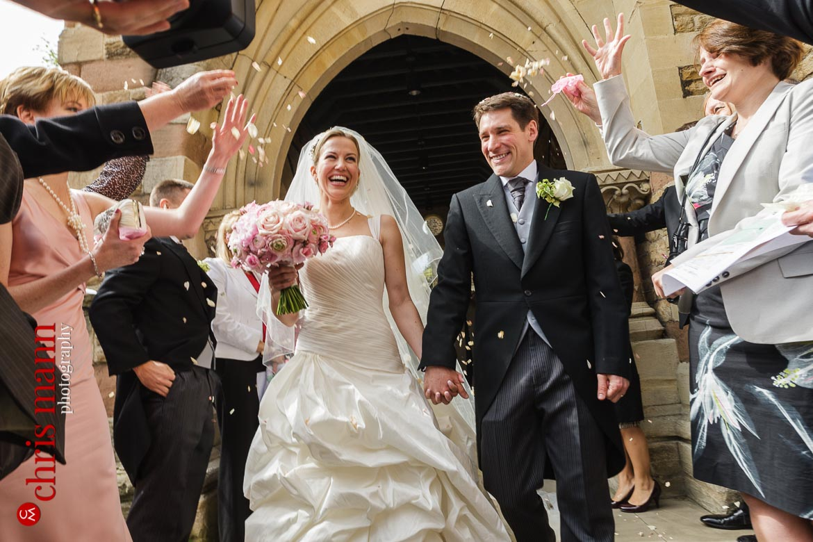 bride and groom leave St George's Church Campden Hil London amid confetti toss