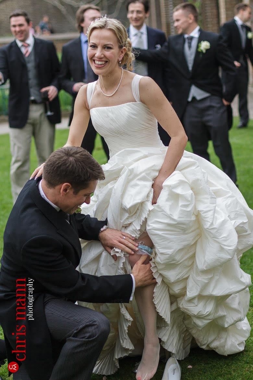 Orangery Holland Park Wedding groom removes bride's garter