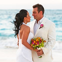 Destination wedding planning tips - couple embracing on beach