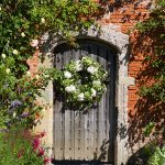 walled garden at cowdray doorway with wreath
