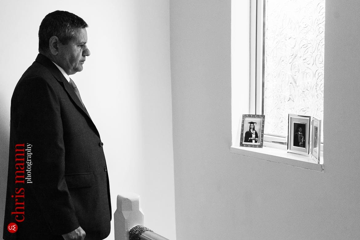 father of bride looks at photos of his children
