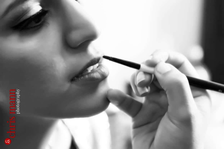 makeup artists applies lipstick to bride