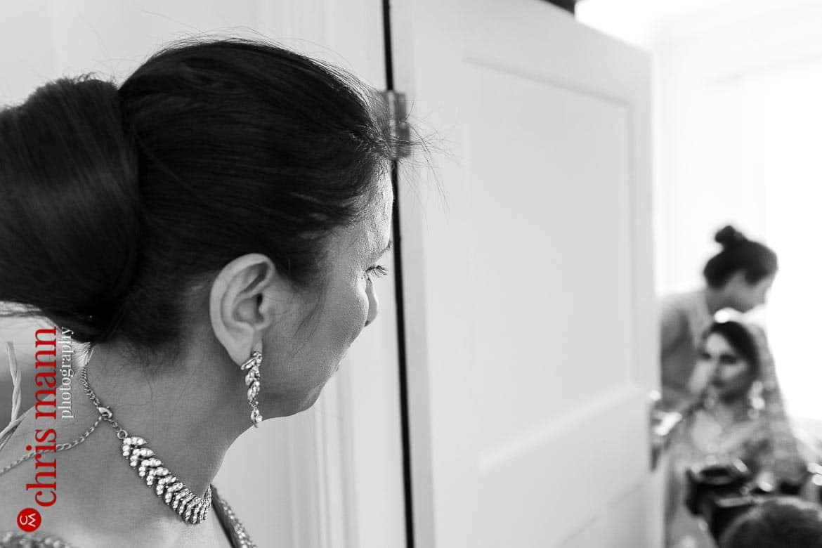 mother of bride watches as her daughter gets ready