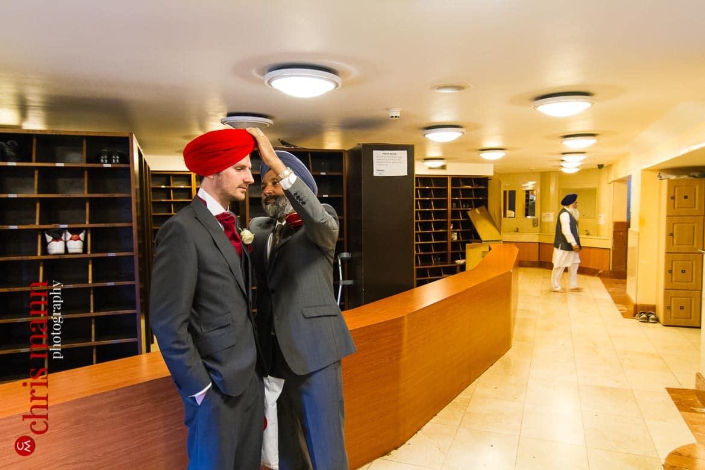 groom's turban is adjusted before Sikh wedding