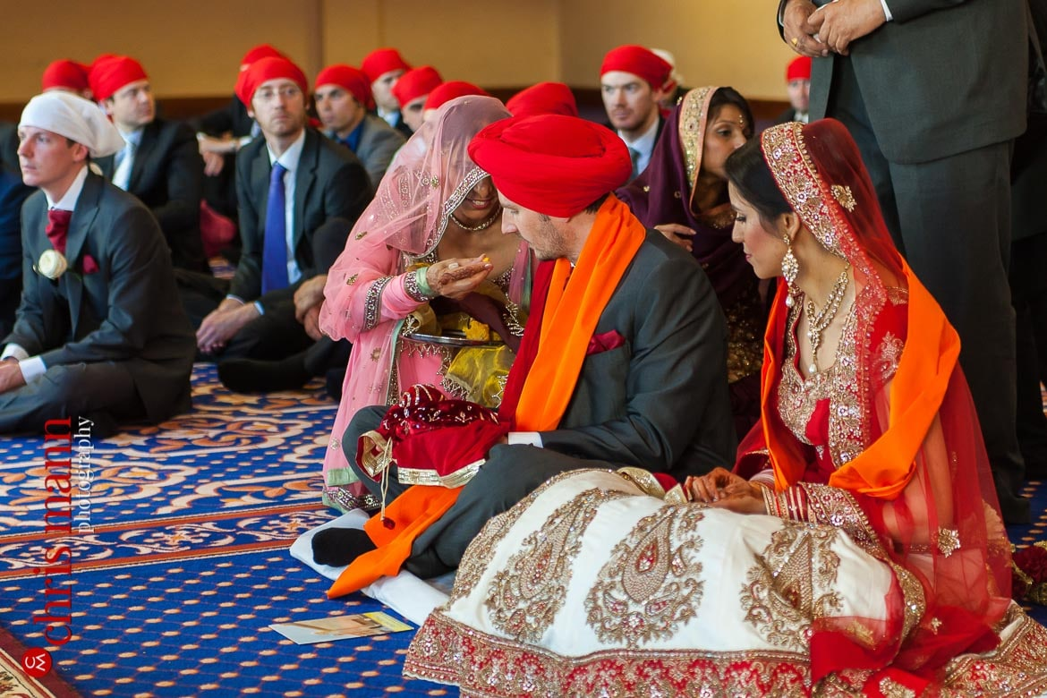 mother of bride feeds groom at Sikh wedding ceremony