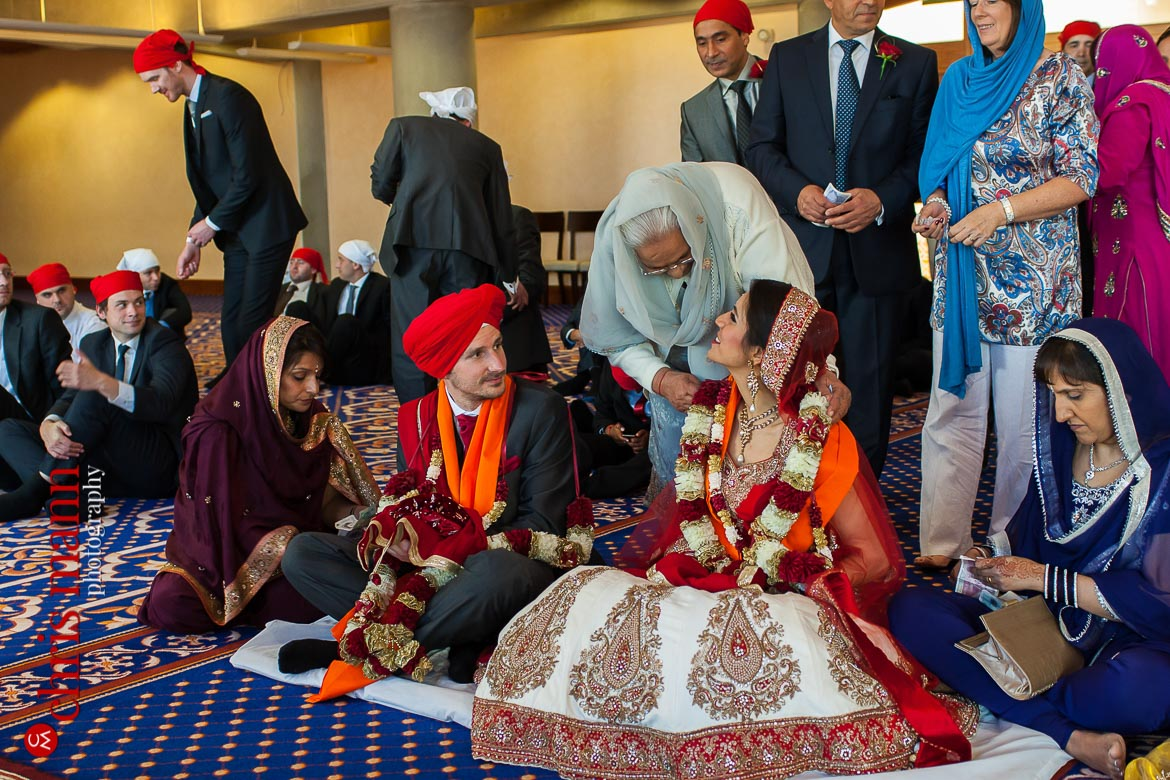 grandmother congratulates bride at Sikh wedding ceremony