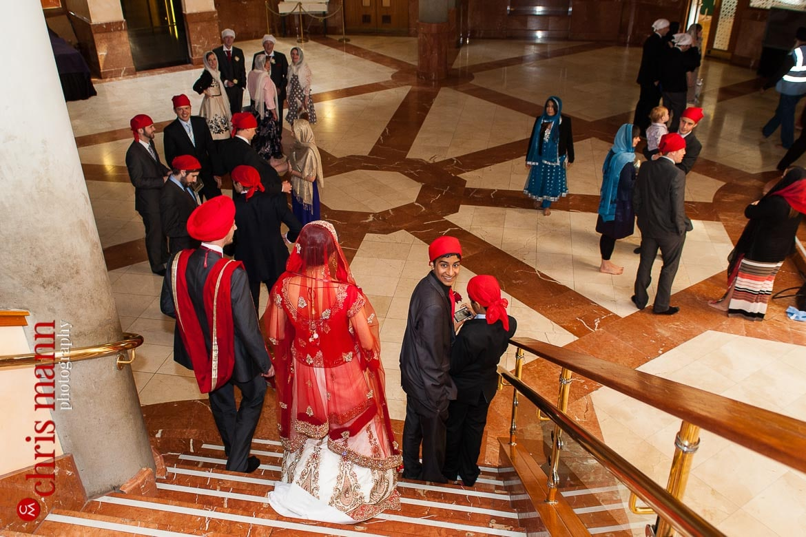 bride and groom descend stairs after Sikh wedding ceremony at Sri Guru Singh Sabha gurdwara Southall