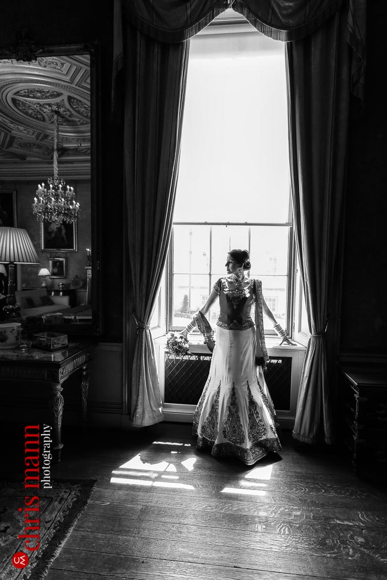 bride poses by window Syon House London wedding