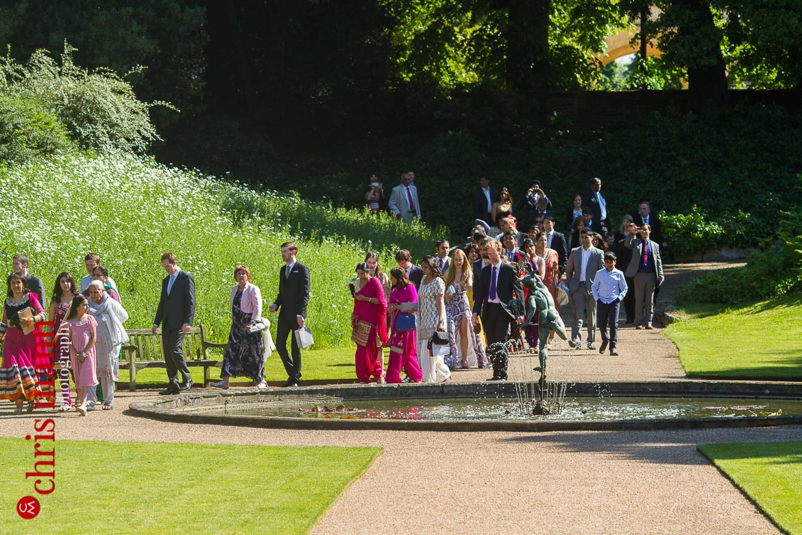 wedding guests walk through gardens to reception at reception Syon Park Great Conservatory