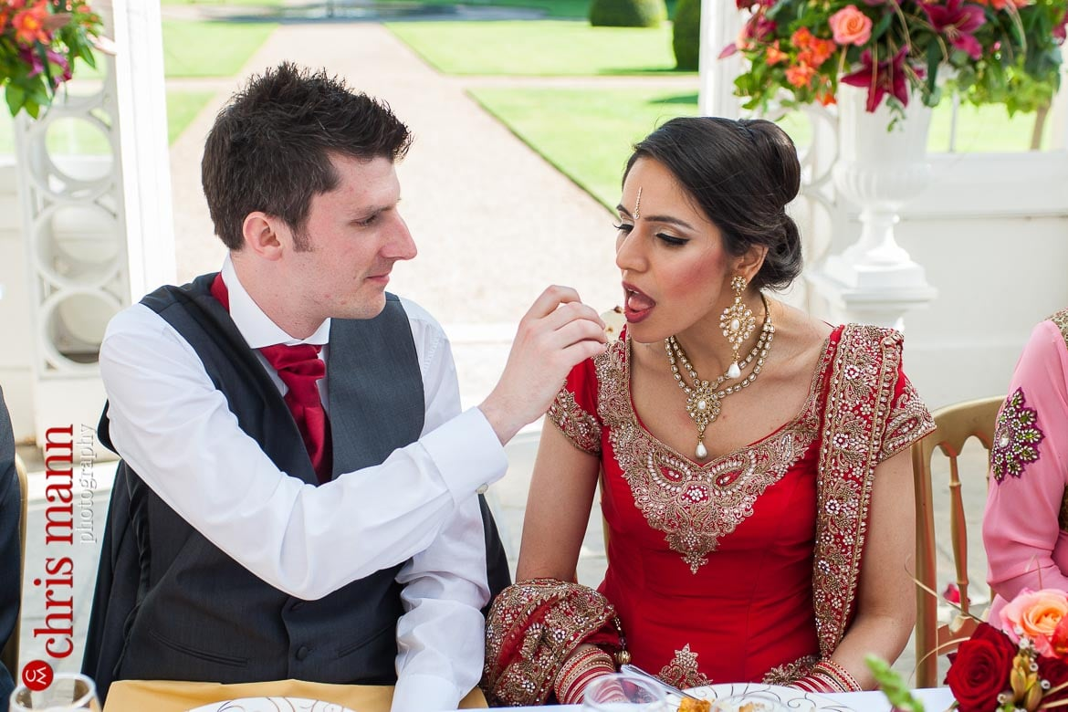 groom feeds bride wedding breakfast at reception Syon Park Great Conservatory