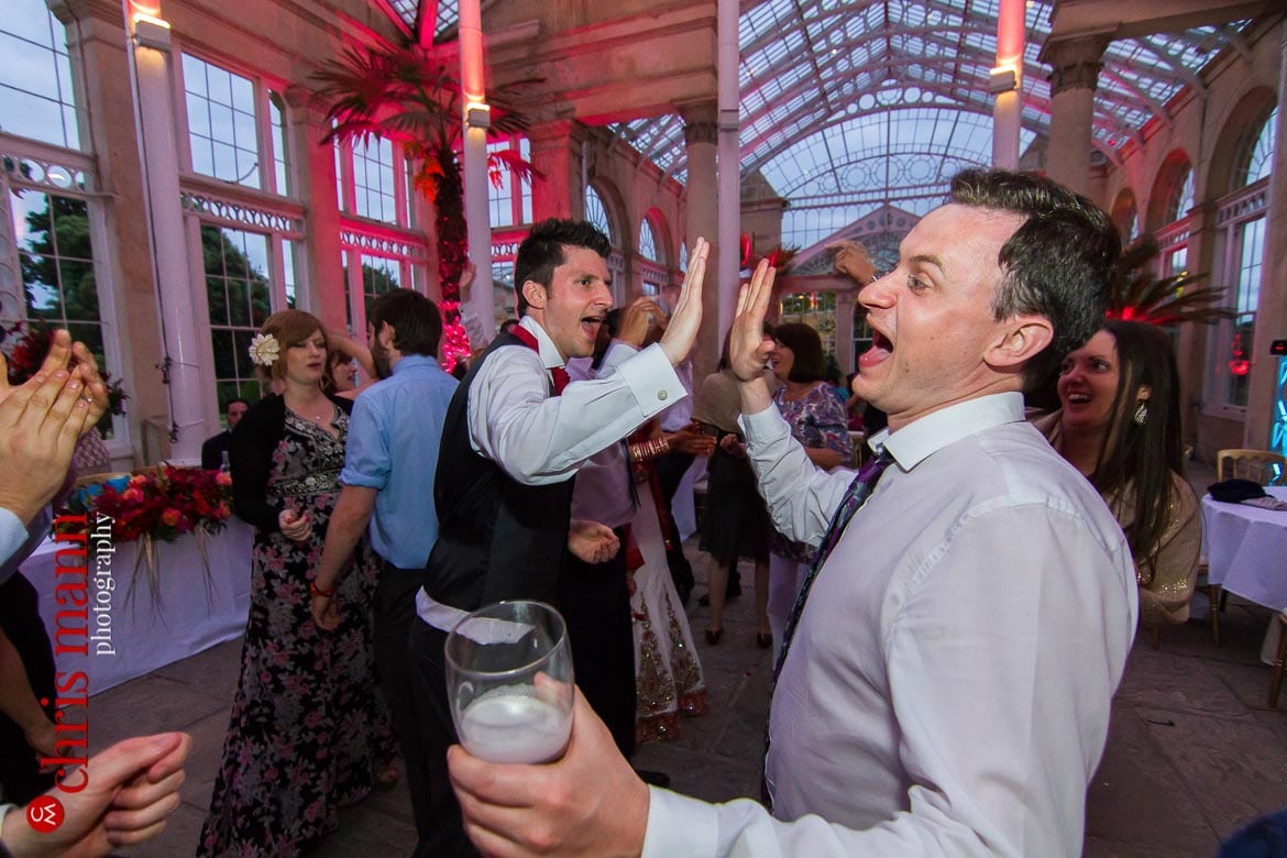 groom high fives with guest at reception Syon Park Great Conservatory