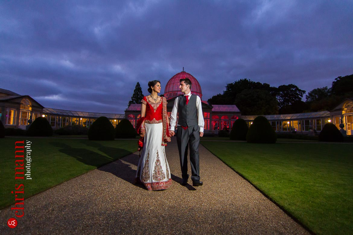 bride and groom walk in gardens at dusk Syon Park Great Conservatory