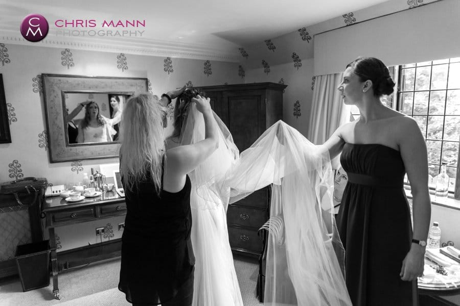 bride in room getting ready dons veil
