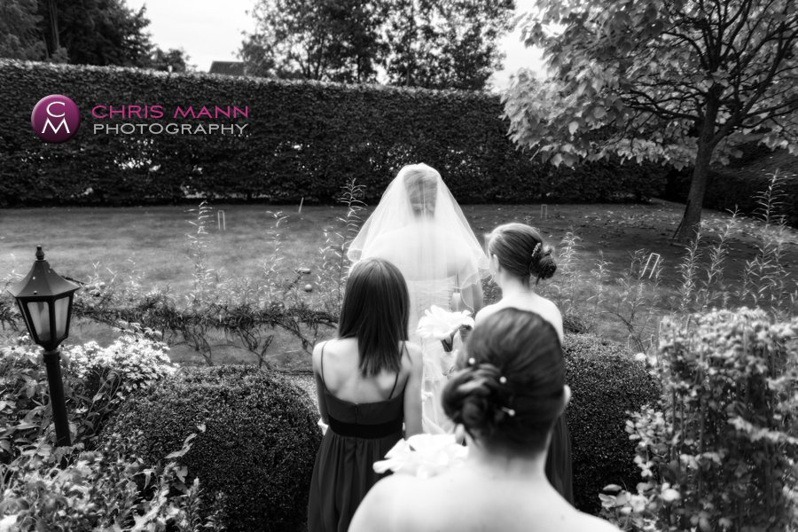 bride and bridesmaids walk through garden on way to wedding