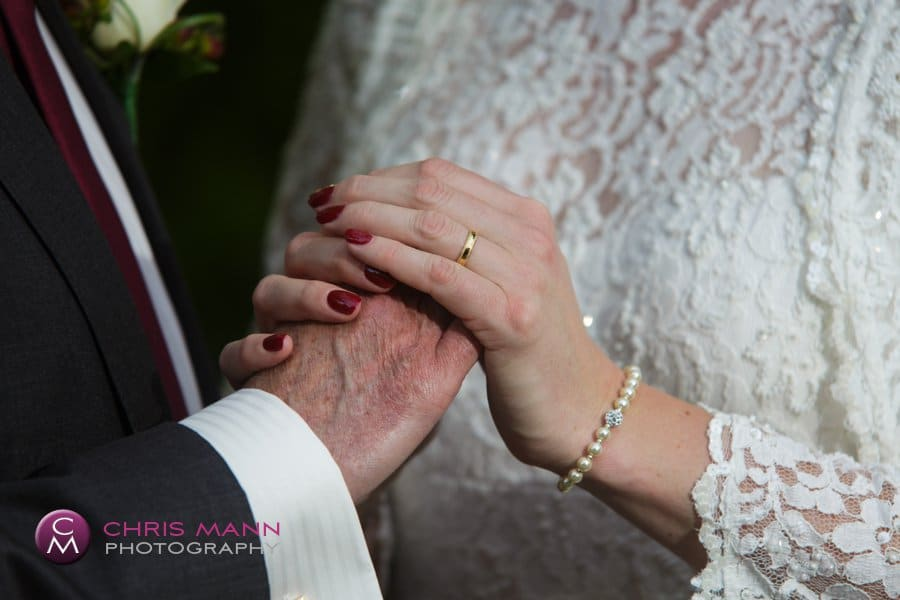 bride and groom hold hands wedding rings