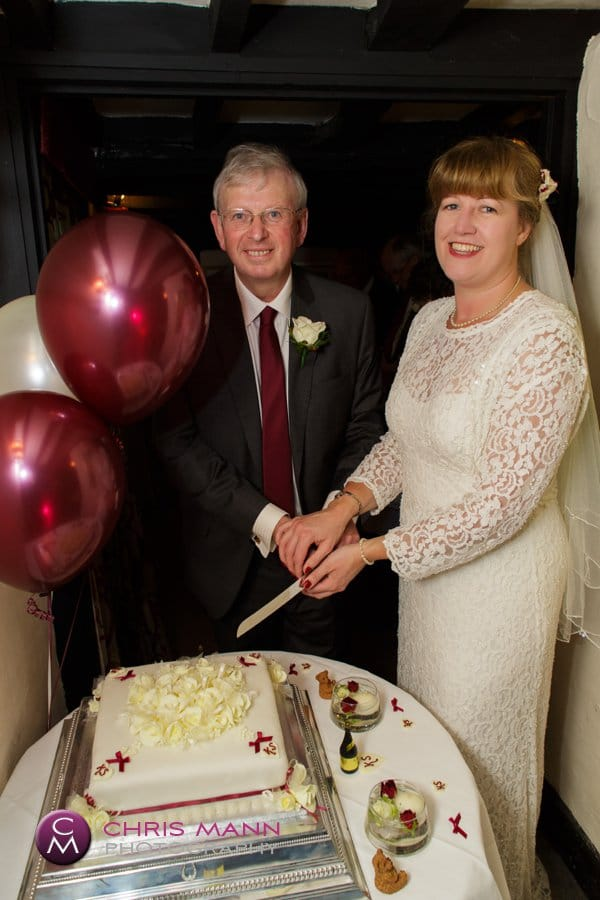 bride and groom cut cake at wedding reception