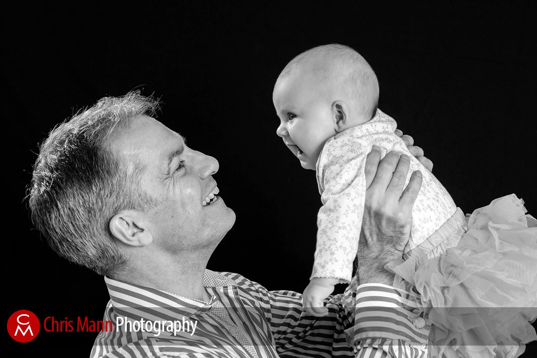 Dad lifts up young baby in his arms smiling