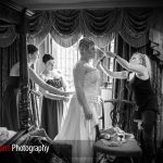 bride getting ready in a bedroomw tih four poster bed at Langshott Manor