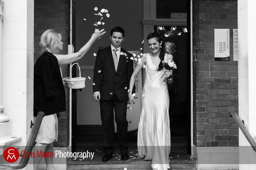 bride and groom exit Mayfair Library wedding to a shower of confetti