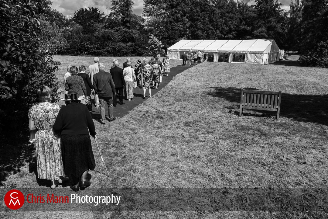 guests walk towards marquee for wedding reception