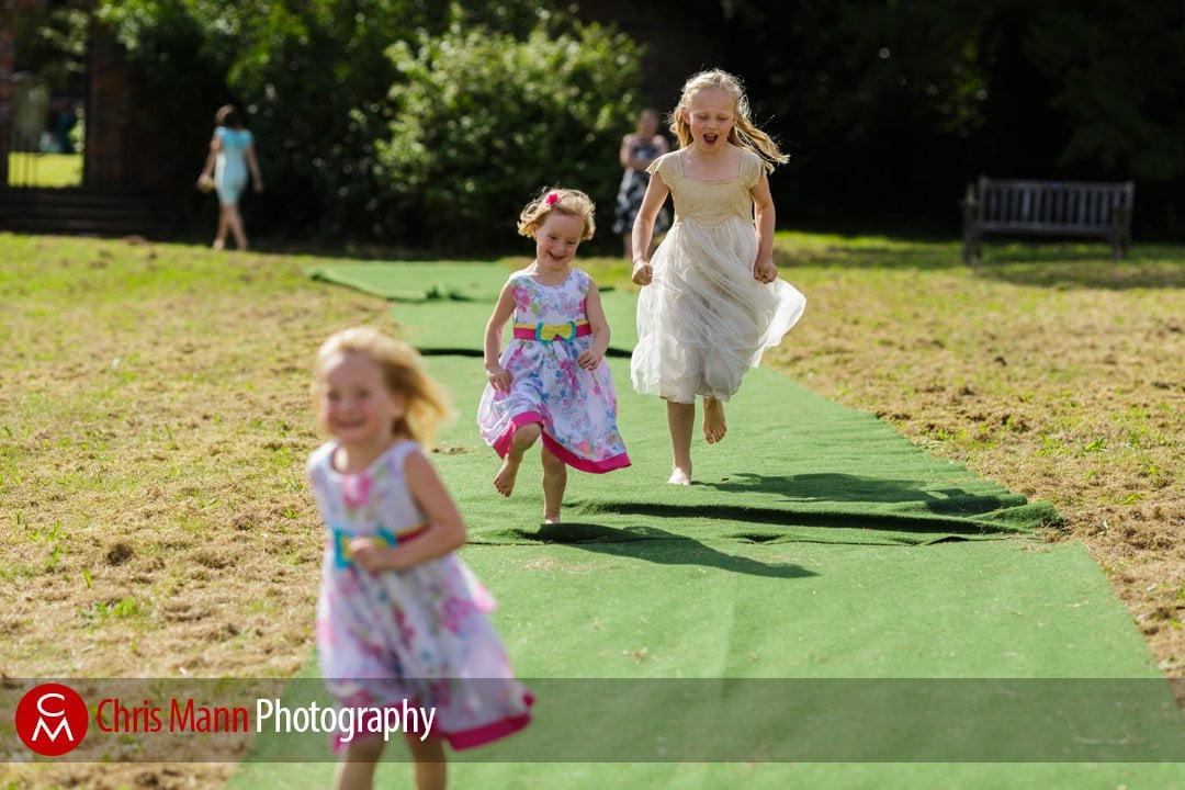 children running on grass at wedding reception