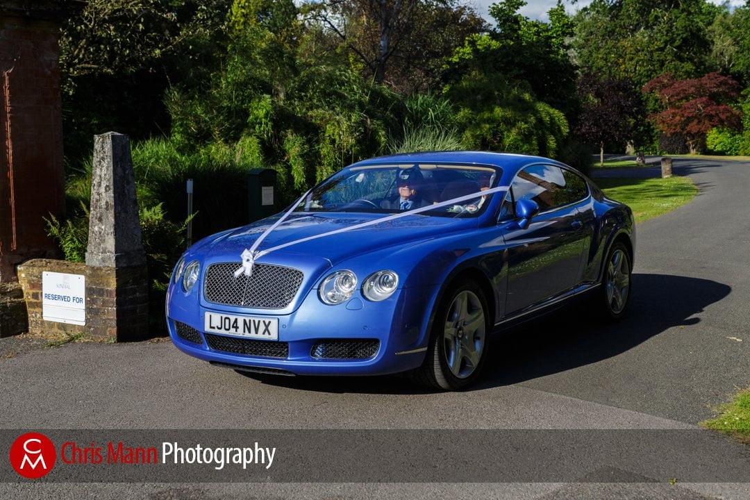bridal car arrives at reception venue blue Bentley