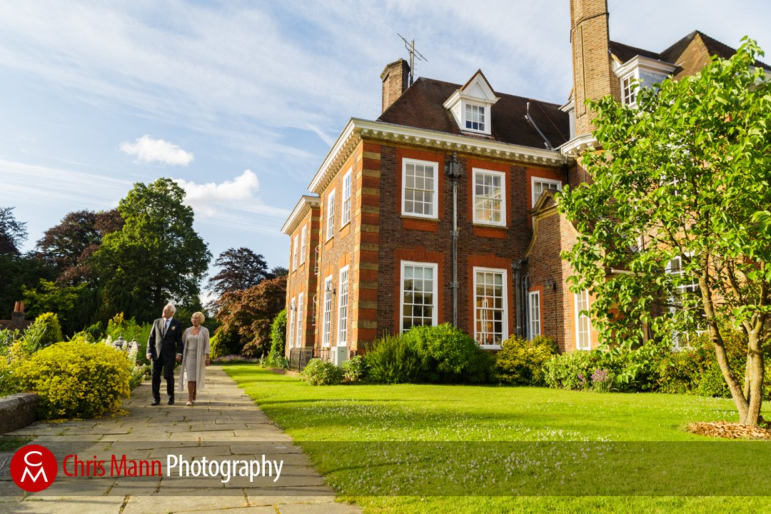 bride and groom walkin in gardens at Barnett Hill Surrey wedding venue