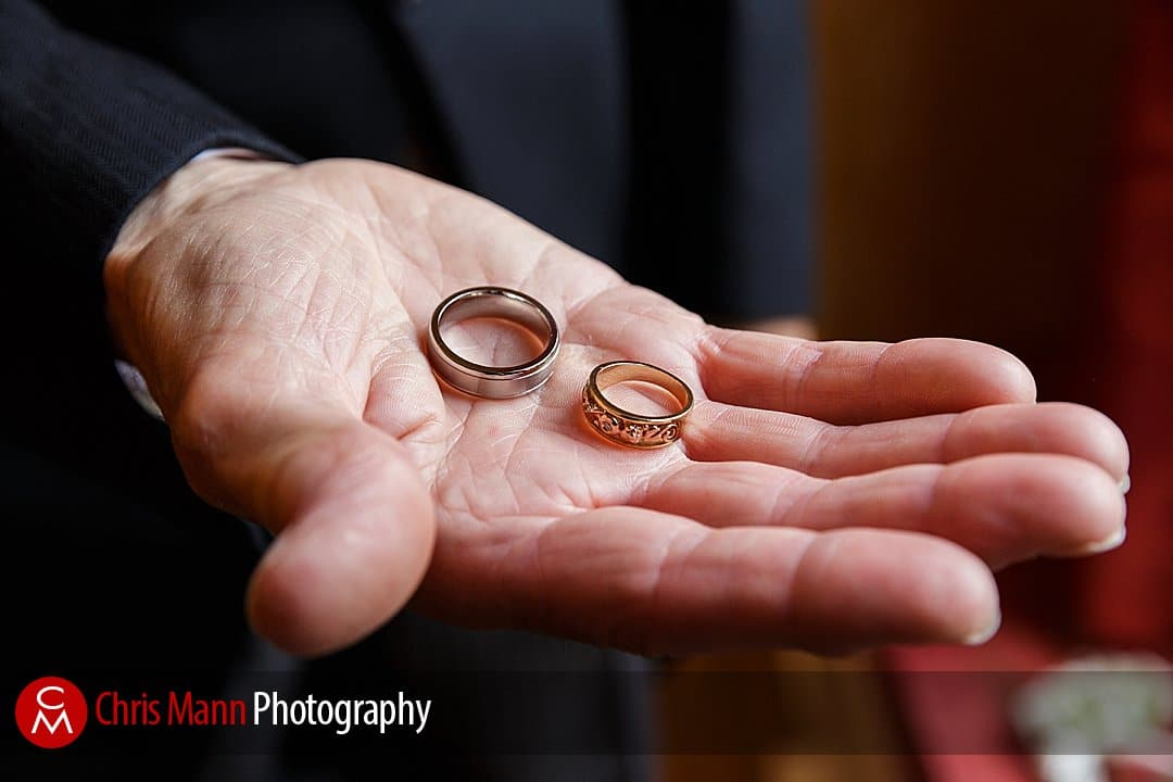 best man holds out rings before wedding at Manor House Hotel Guildford
