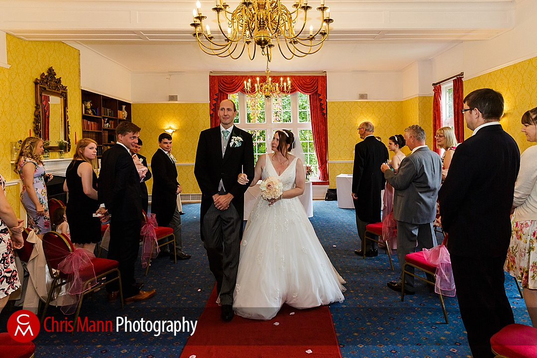 bride and groom process down the aisle Manor House Hotel Guildford