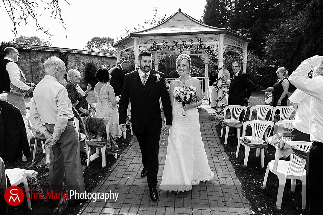 smiling bride and groom walk down aisle outdoor wedding Manor House Hotel Guildford