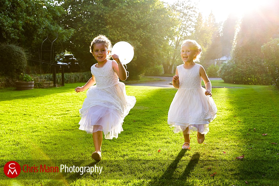 flower girls bridesmaids run with balloons sunny wedding Guildford Surrey