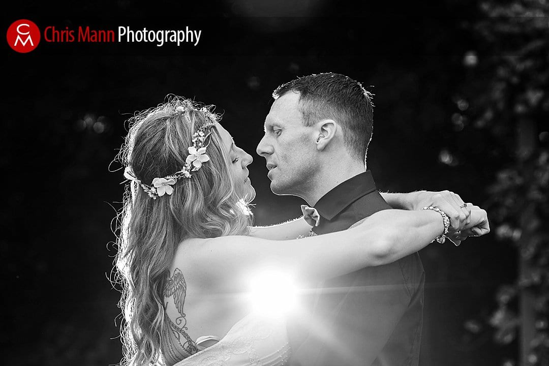 bride and groom hug with flash starburst black and white photo