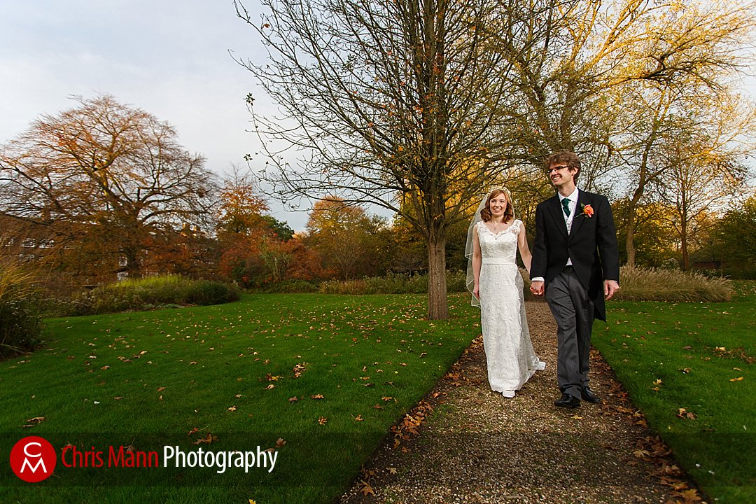 bride and groom walking in gardens Lady Margaret Hall Oxford wedding photos