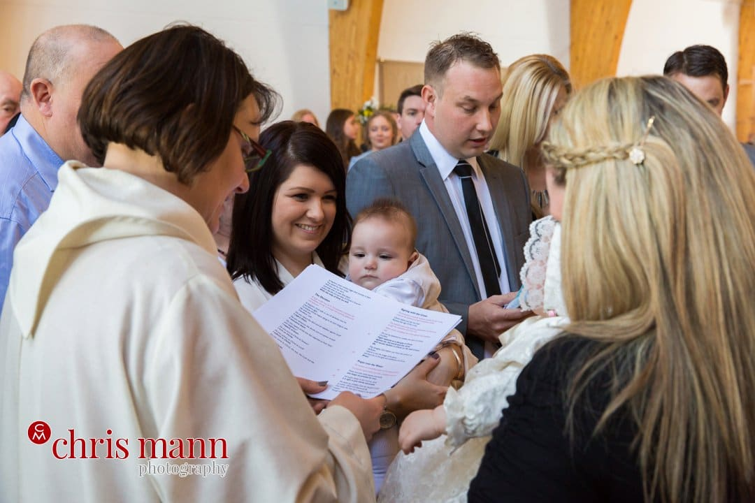 minister reads blessing at font christening