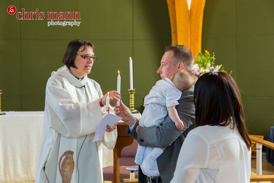 minister hands candle to father christening ceremony