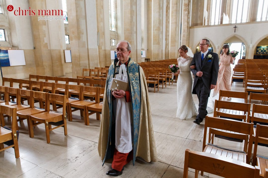 minister bride and father process down nave Guildford Cathedral