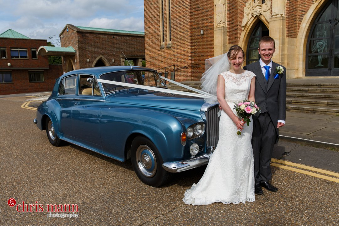bride and groom with Bentley car Guildford Cathedral