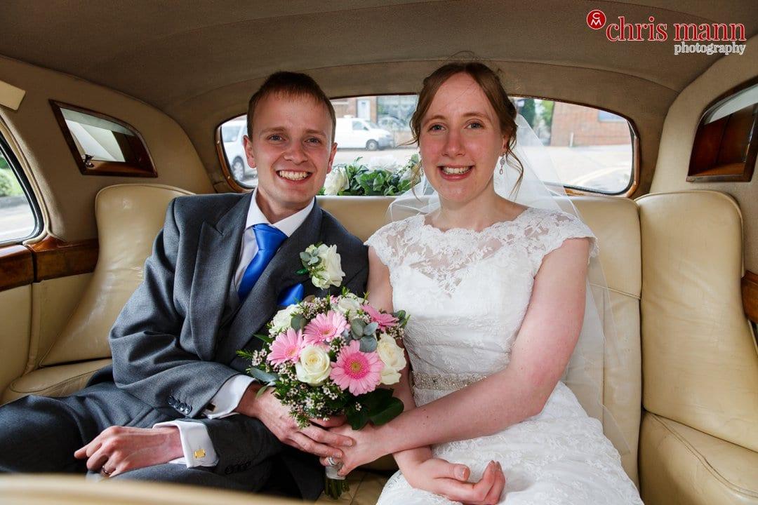 bride and groom in bentley car