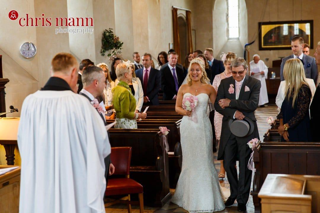 bride walks down the aisel t Luke's Church Burpham Guildford Surrey