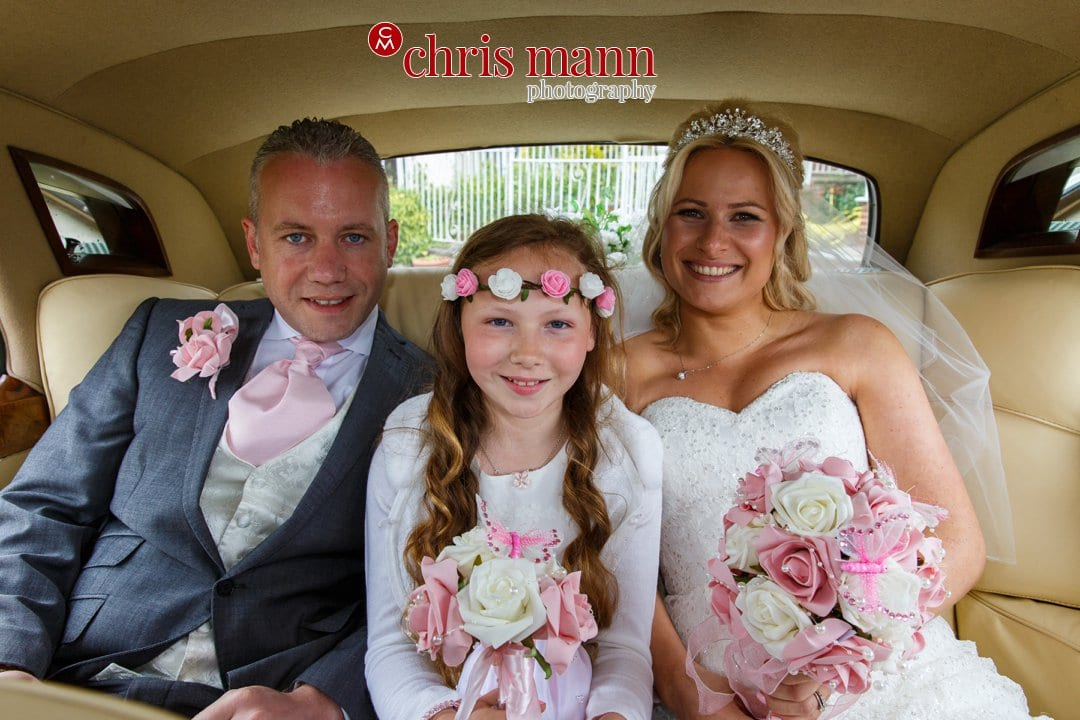 bride and groom in car with bridesmaid flower girl