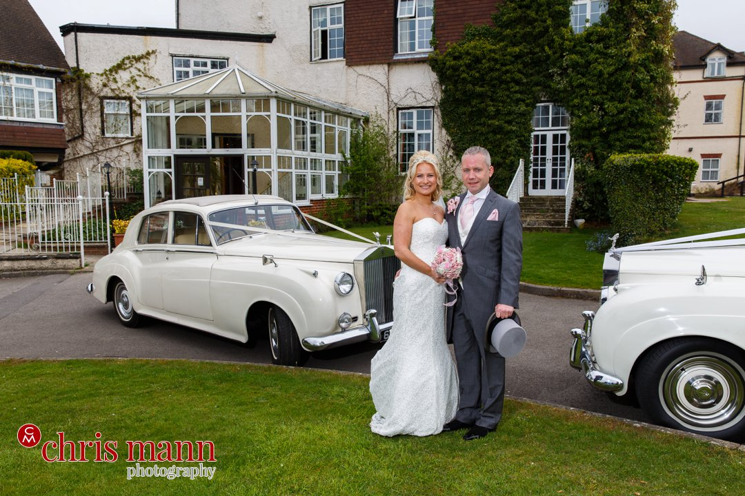 bride and groom pose with wedding cars Guildford Wedding photography Manor House Hotel