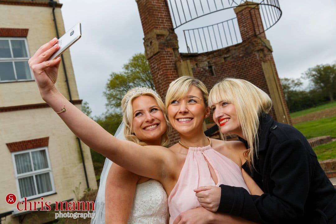 bride and bridesmaids take selfie