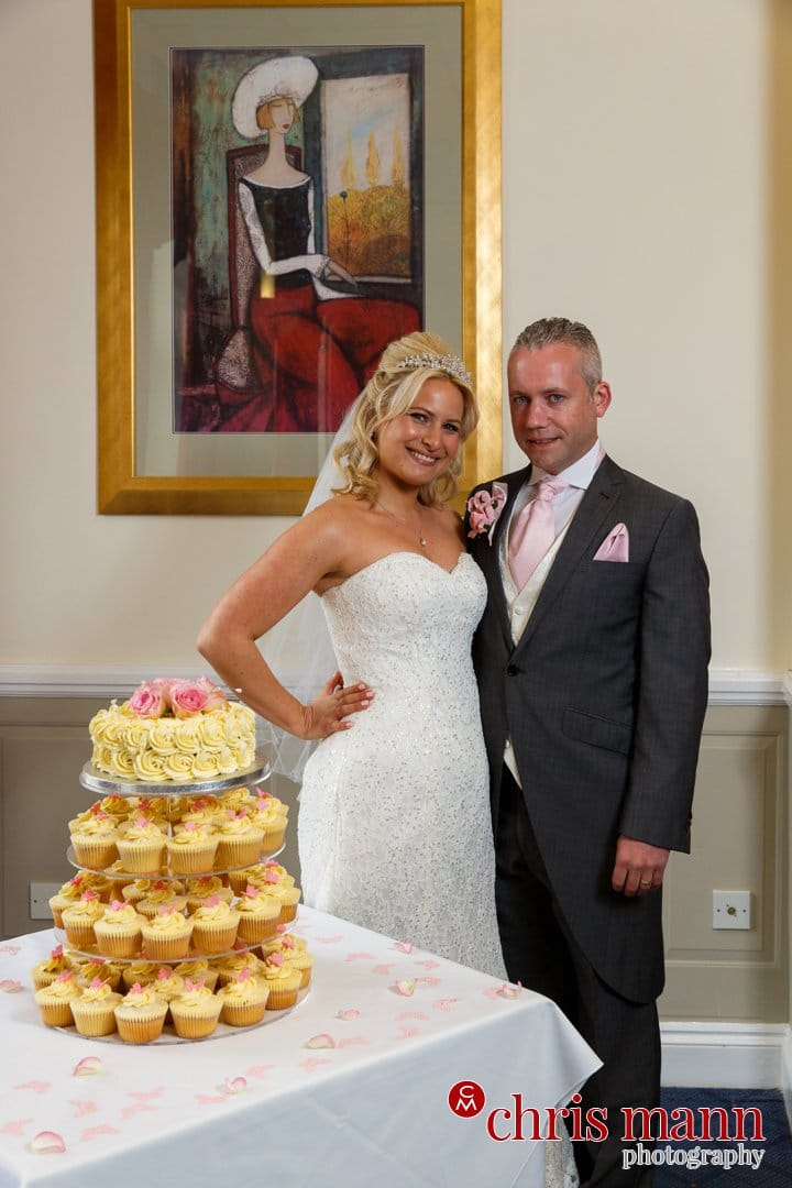 bride and groom pose with wedding cake