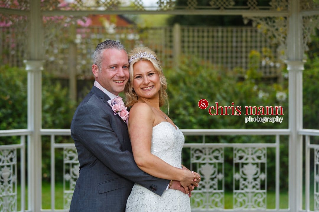 bride and groom in gazebo Manor House Hotel Guildford