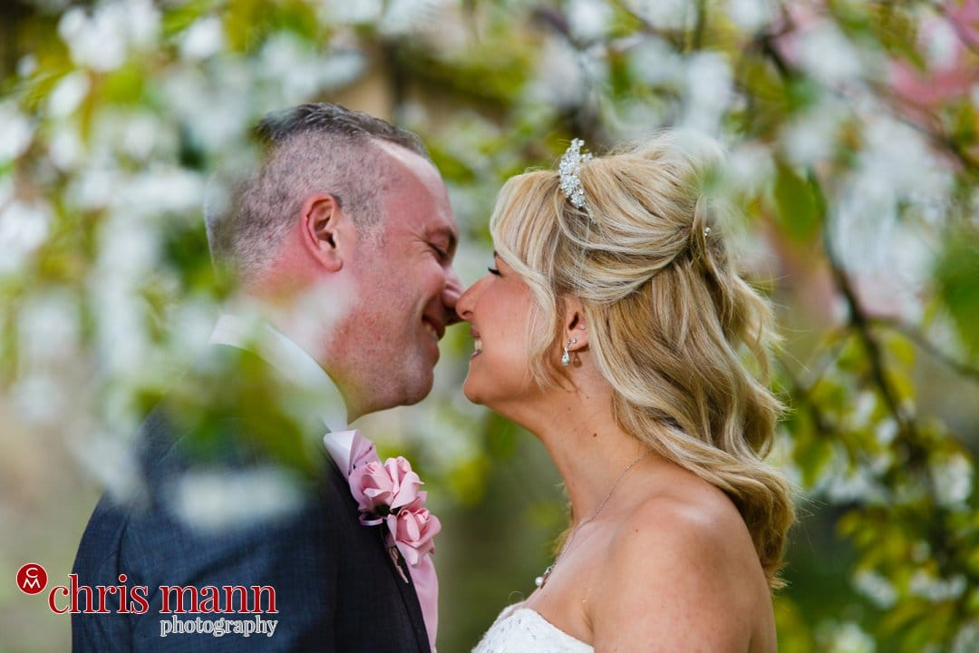 bride and groom kiss under cherry blossom