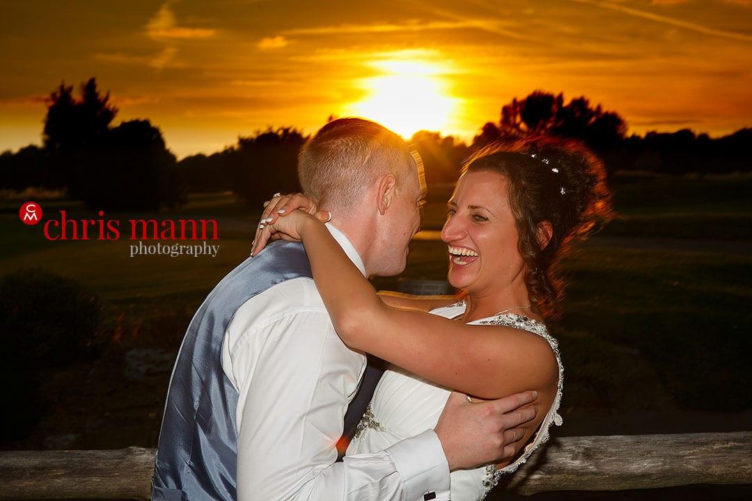 bride and groom hug at sunset surrey downs golf club wedding