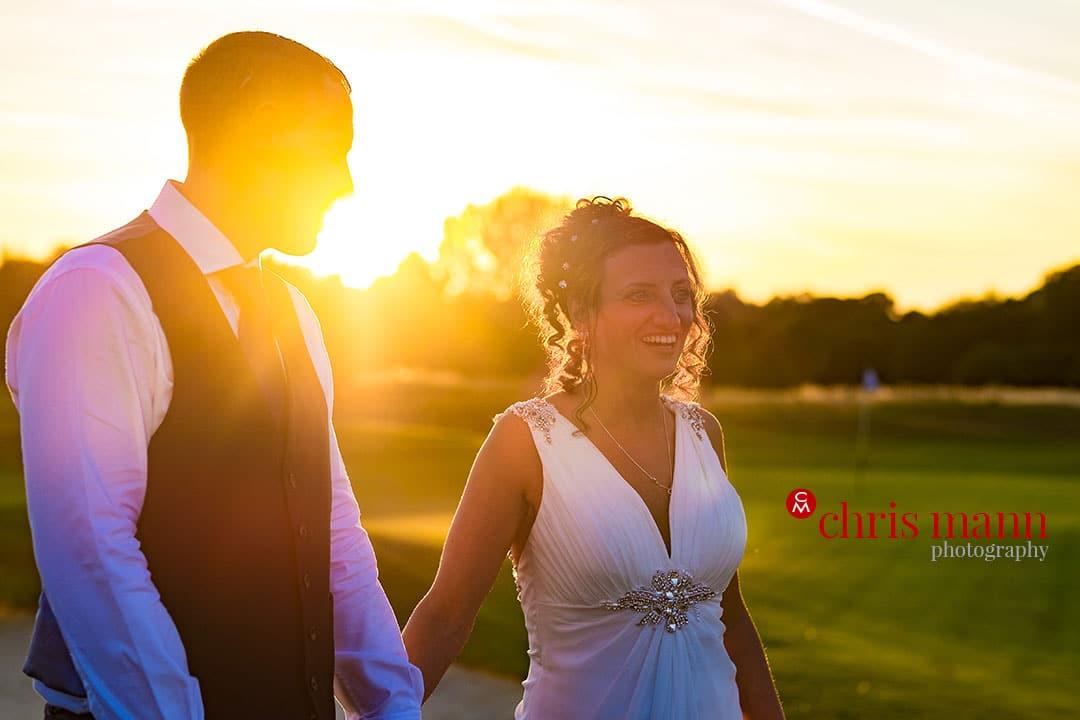 bride and groom walking sunset surrey downs golf club wedding